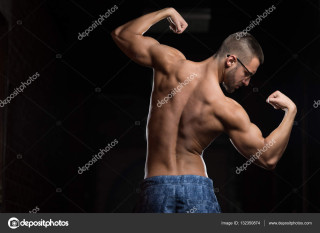 Muscular Geek Man Flexing Muscles In Gym